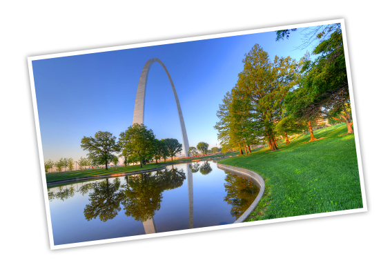 The Gateway Arch standing tall over a pond in a tree-filled urban park
