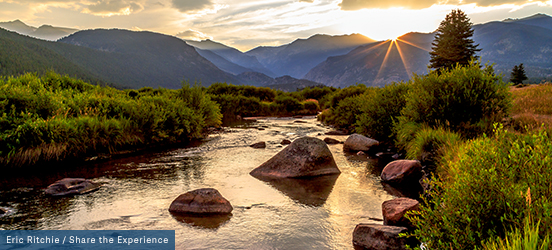 A shallow stream flows around rocks, through a valley in Rocky Mountain National Park, large peaks are silhoutted in the distance and the sun sets behind them