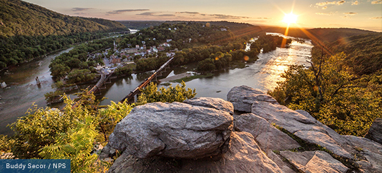 A view from Maryland Heights Overlook Trail onto the town of Harpers Ferry, the river that flows around it, and trees covering the land all around