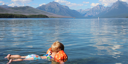 A little boy wears floats while he swims on a lake with mountains lining the horizon in Yellowstone National Park