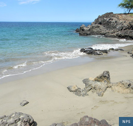 A view of the sandy beach with clear ocean water, edged with volcanic rock