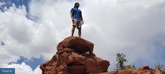 A man stands on top of a pile of red rocks, appearing to tower over his surroundings in Captiol Reef National Park