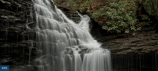 A waterfall flows over a tall rock wall, formed by many visible rock layers, each creating a mini waterfall.