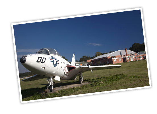 A World War Two plane sits in front of a red brick hanger at Tuskegee Airmen National Historic Site