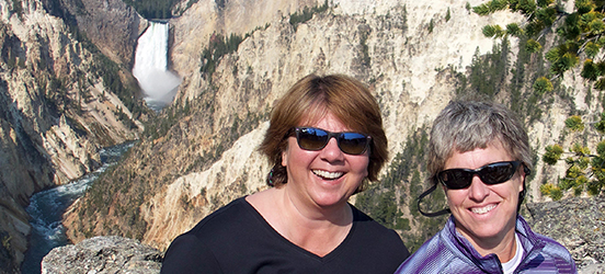 Barbara and Jayne smile with the Upper Falls of Yellowstone National park in the background