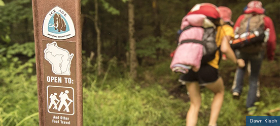 A trail marker sign from the Ice Age National Scenic Trail is in focus with a blurry background of tall vegetaion along the trail and two hikers walking with their gear