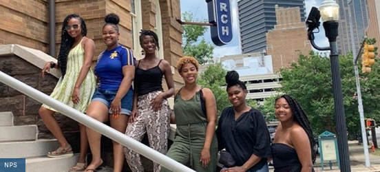 Six Black women, who were the producers of the Twenty & Odd video from NPS, each stand on a stair of the 16th Street Baptist Church in Birmingham, Alabama