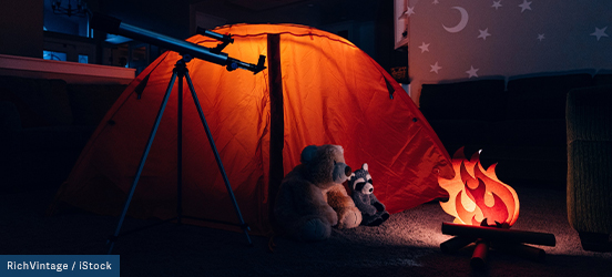 Inside a home, with the lights turned off, a small tent glows, a teddy bear and racoon toy sit in front of a fake fire, a paper moon and stars can be seen on the wall, and a telescope stands to the side