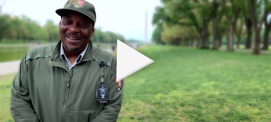 A still image taken from the Thank You video that shows a park ranger smiling while standing on the National Mall with the Washington Monument barely visible in the background
