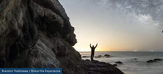 A person stands on a large rock with their arms raised as they look out onto a starry night sky just as the last bit of orange from the sunset disapears into the glimmering silver of the Pacific Ocean