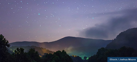 Bright stars seem to twinkle above forest-covered hills of Blude Ridge Parkway