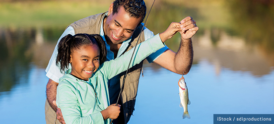 A little girl proudly smiles at the camera while her father helps her hold up her fishing pole with a small fish caught at the end
