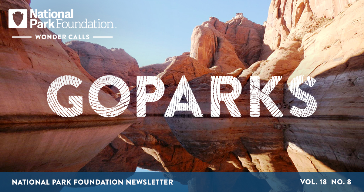 National Park Foundation, GoParks newsletter graphic cover image of the still blue river flowing through the tall, red, layered canyoon walls of Glen Canyon Recreation Area
