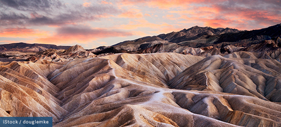 The rolling sand covered peaks and valleys illuminated pink from the sunset at Death Valley National Park