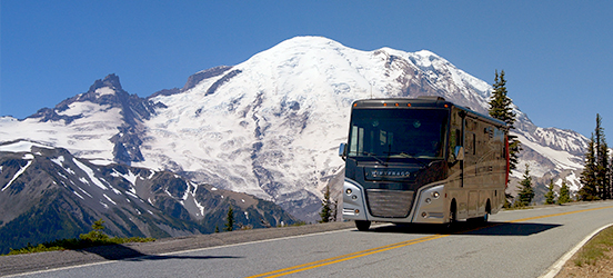 A Winnebago camper driving down a road with a snow covered mountain peak behind it in Mount Rainier National Park