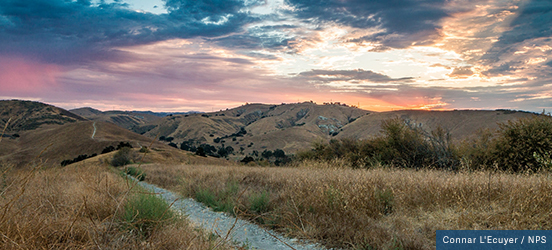 From a hiking trail at the top of a hill, the viewer can see many rolling mountain tops during a pink and orange sunset in Santa Monica Mountains National Recreation Area