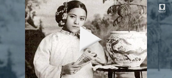 A still image taken from the Women In Parks video of a historic photo Tye Leung Schulze posing while sitting in a chair, next to a wooden side table with a plant in a painted pot, a backdrop is behind her picturing trees and other plants
