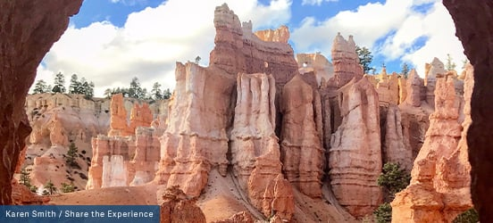 Visible through a cavern opening are tall, spire-shaped rock formations, some dotted with trees in Bryce Canyon National Park