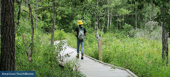 A service corp volunteer wears a yellow hard hat and backpack while walking down a boardwalk surrounded by thick vegetation