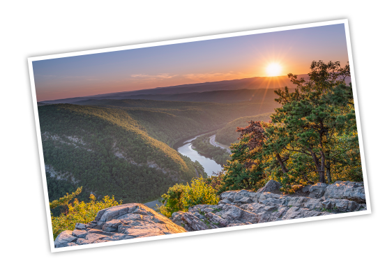 A hill-top view, overlooking the tree covered hills lining the Delaware River during sunset at the Delaware Water Gap National Recreation Area