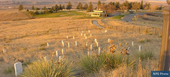 A cemetery with small white headstones is fenced off in the fields at Little Bighorn Battlefield National Monument