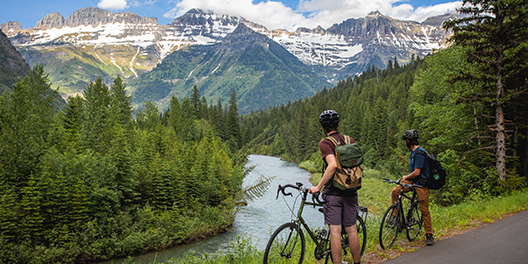 Two people stand at the edge of a trail, next to their bicycles to take in the view of a river flowing through evergreens with snow-tipped mountain peaks in the distance in Glacier National Park