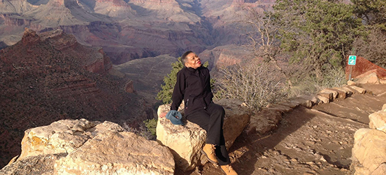 Audrey Peterman sits on a boulder, leaning back to soak in the sun on a trail in Grand Canyon National Park, the gorgeous view of the canyon fills the image behind her