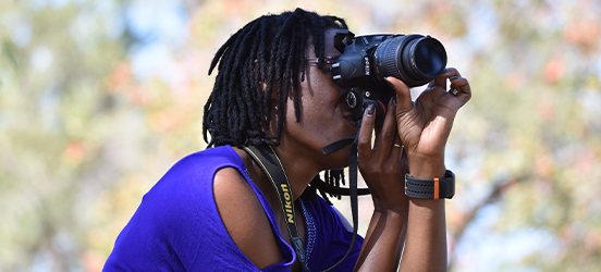 A woman crouches in a park as she aims her camera for a shot