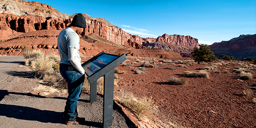 A man reads a National Park Service informational sign at the side of a gravel trail at the foot of canyons in Capitol Reef National Park