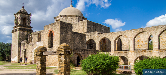 The Spanish Mission main structure with a domed center, a corner tower, and many large, arched openings in the limestone walls