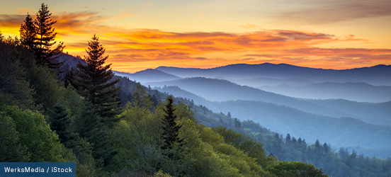 A view of the sunset and rolling blue mountains from a peak in Great Smoky Mountains National Park