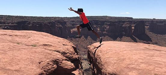 A person jumps over a gap in a large rock formation, part of a huge canyon visible behind them