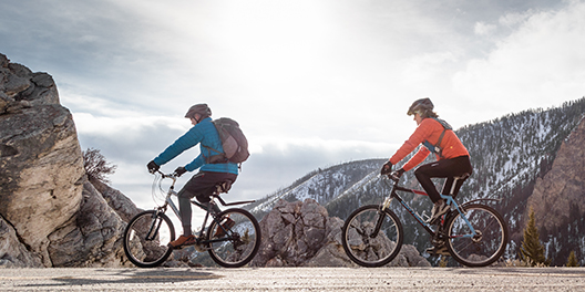Two cyclists bike along a mountain road lined with large boulders, between which a view of snow dusted mountains can be seen in Rocky Mountain National Park
