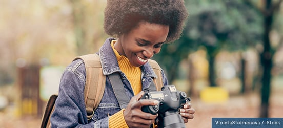An African American woman smiles at the pictures she's taken on her camera, a blurry park can be seen behind her