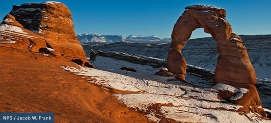 Snow dusts the red rock of the delicate arch and huge canyons in Arches National Park
