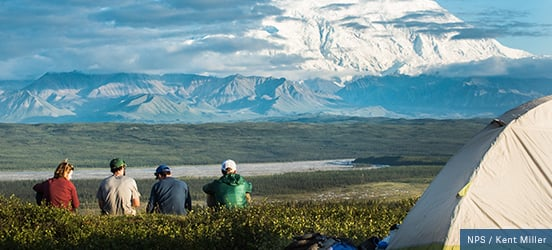 A group of four campers sit on a grassy hill, with their tent behind them, looking out at the large, snow covered mountains in Denali National Park