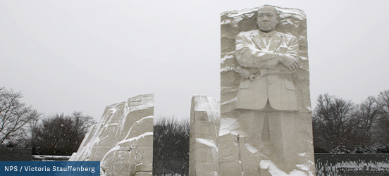 The Martin Luther King Jr. Memorial on the National Mall is lightly dusted with snow stands tall in front of bare trees and a white, winter sky behind.