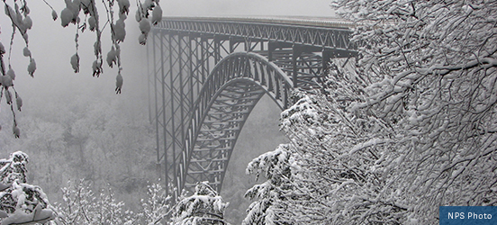 The iron bridge the crosses New River Gorge National River is hazy through the fog and icy trees