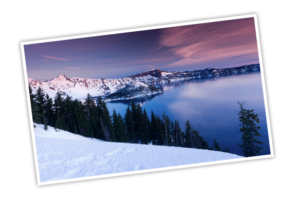A line of snowy mountains that form the edge of Crater Lake with a long cluster of evergreen trees in the foreground and a pink and blue sky above, taken in Crater Lake National Park