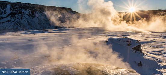 The sun flares through steam rising from snow covered hot springs in Yellowstone National Park