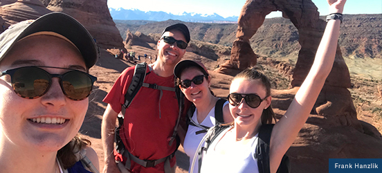 The Hanzlik family smiles for a selfie in front of the Delicate Arch at Arches National Park
