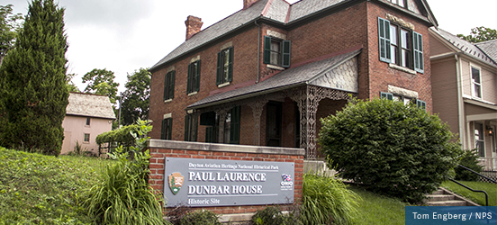 A two story, brick house that was once the home of Paul Laurence Dunbar, marked by an NPS sign in the lawn by the sidewalk