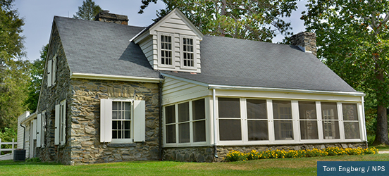 A two story house with natural stone exterior and a screened-in porch is the former home of Eleanor Roosevelt and now honored as a national historic site