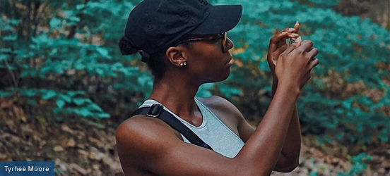 Journee Harris holds her phone up to take a picture of something to her side while in a wooded area at Rock Creek Park