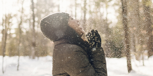 A woman grins with her head thrown back to let snow fall onto her face