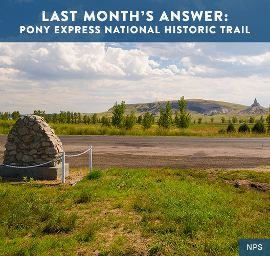 A monument, created by stones piled into a dome, is the roadside marker for the Chimney Rock Pony Express Station. Chimney Rock can be seen on the horizon, past a field with bluffs to its side
