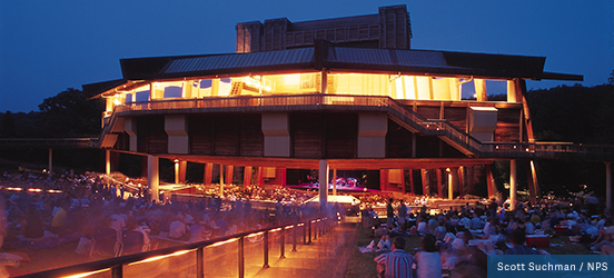 In the evening the outdoor theatre casts a warm glow on the audience sitting on a grassy, tiered steps at Wolf Trap National Park for the Performing Arts