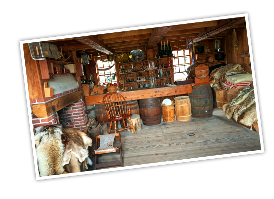 The inside of a supply store at Fort Stanwix National Monument that has barrels supporting a checkout counter, piles of animal fur, floor to ceiling shelves filled with jars and other items, and a brick fireplace
