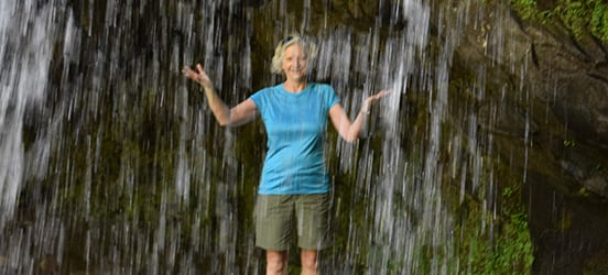 Louise Wiedermann stands in a rocky alcove just behind a waterfall