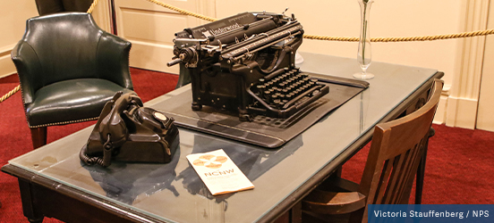 On a glass-top desk sits a black rotary phone and a black typwriter, located in Maggie L. Walker National Historic Site